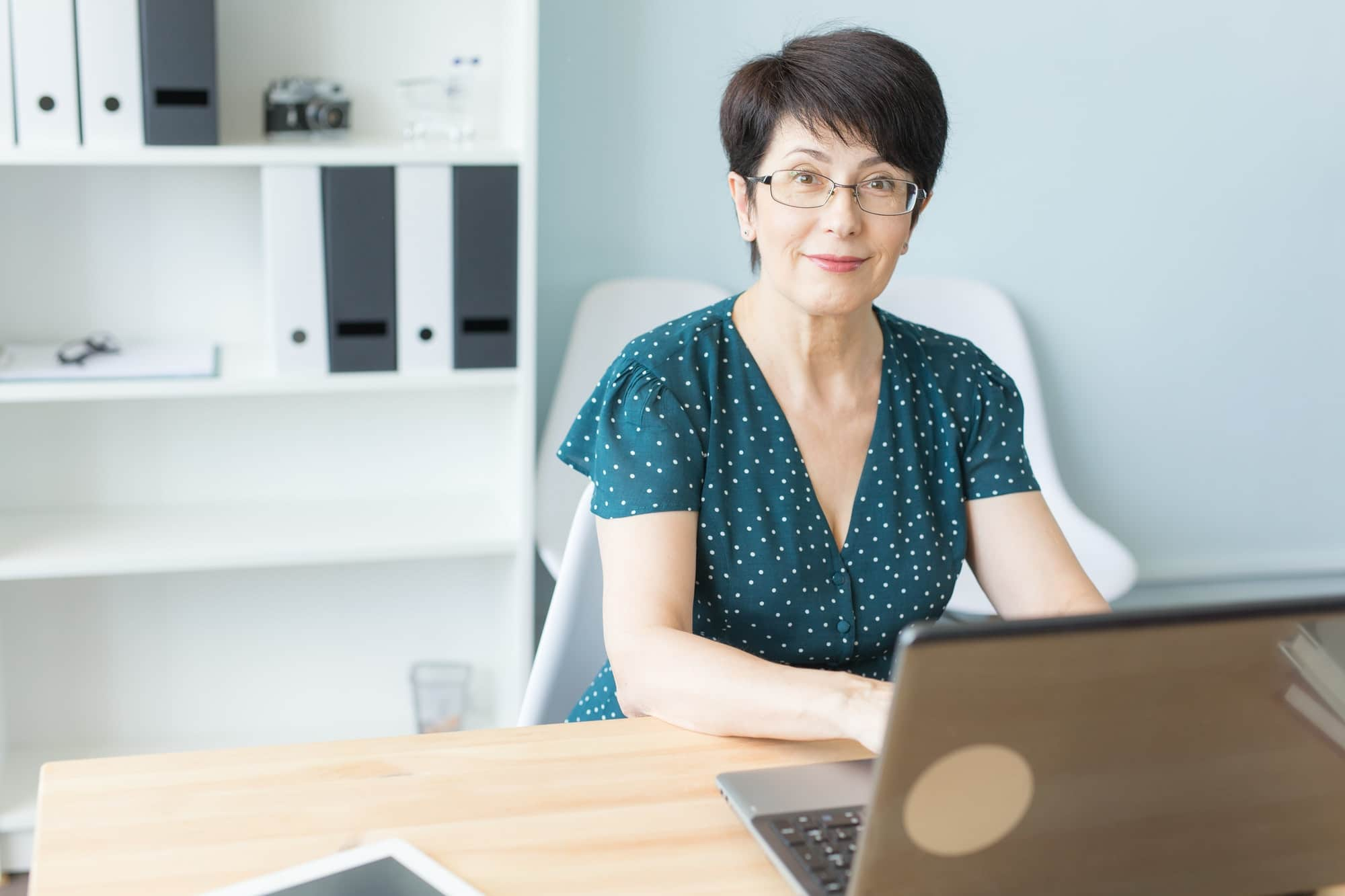 Business, technology and people concept - middle aged woman work in office and use a laptop